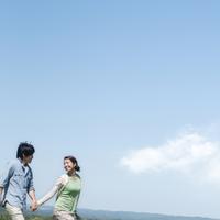 手をつなぎ微笑むカップル