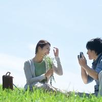 草原に座り写真を撮るカップル