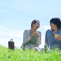 草原に座り談笑するカップル