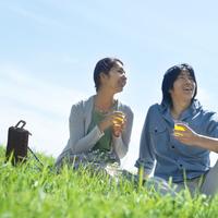 草原に座りジュースを飲むカップル
