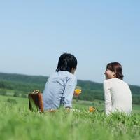 草原に座りジュースを飲むカップルの後姿