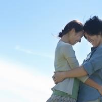 青空の下で抱き合うカップル