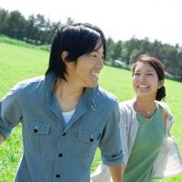 草原で手をつなぎ微笑むカップル