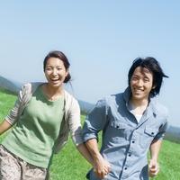 草原で手をつなぎ走るカップル