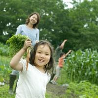 農園で野菜を持ち微笑む親子