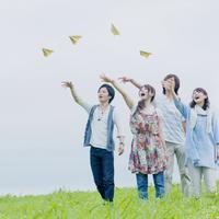 紙飛行機を飛ばす4人の若者たち