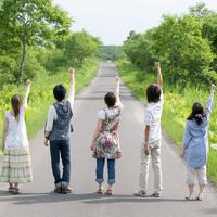 一本道で片手を上げる5人の大学生の後姿
