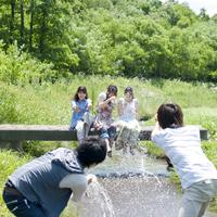 小川で水をかけて遊ぶ5人の大学生