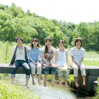 橋に一列に並び微笑む5人の大学生