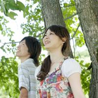 木のそばで微笑む2人の大学生