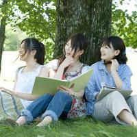 木に寄りかかり微笑む大学生