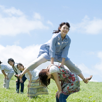 草原で馬跳びをする5人の大学生