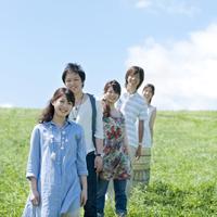 草原で一列に並び微笑む大学生