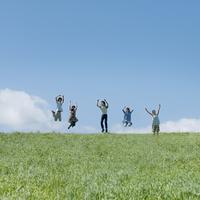 草原でジャンプをする5人の大学生
