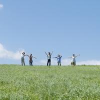 草原で両手を広げる5人の大学生