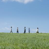 草原を歩く5人の大学生