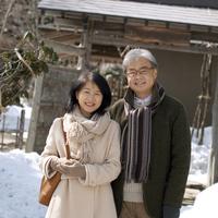 家の前で微笑むシニア夫婦