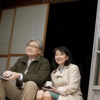 縁側に座りお茶を飲むシニア夫婦