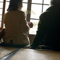 和室でお茶を飲むシニア夫婦の後姿