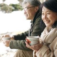 縁側でお茶を飲むシニア夫婦