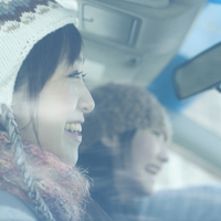 車のガラス越しに微笑む女性
