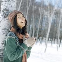雪原でカフェオレボウルを持ち微笑む女性