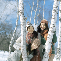 白樺の木の間から顔を出す3人の女性