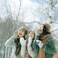 雪原で口元に手をあて微笑む3人の女性