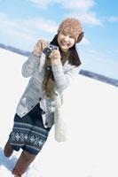 雪原でカメラを構える女性 20027007334| 写真素材・ストックフォト・画像・イラスト素材|アマナイメージズ