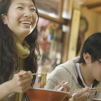 食堂でラーメンを食べ微笑む女性