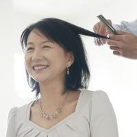 美容室で髪を切ってもらうシニア女性