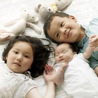 赤ちゃんの側に寝転ぶ子供たち 20027007442| 写真素材・ストックフォト・画像・イラスト素材|アマナイメージズ