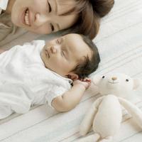寝ている赤ちゃんの隣で微笑む母親