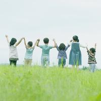 草原で手をつなぐ子供たちの後姿