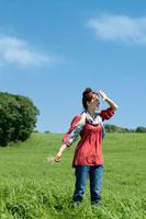 草原で空を見上げる女性