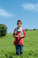 草原で野花を持ち微笑む女性
