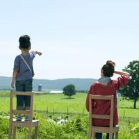 椅子に座り草原を眺める親子の後姿