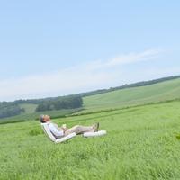 草原で椅子に座りリラックスをするシニア男性