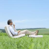 草原で椅子に座りコーヒーを飲むシニア男性