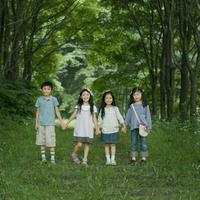 森で手をつなぎ微笑む4人の子供たち