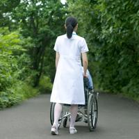 患者の乗る車椅子を押す看護師の後姿