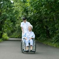 患者の乗る車椅子を押す看護師