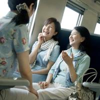 電車の中で笑顔の親子とシニア女性