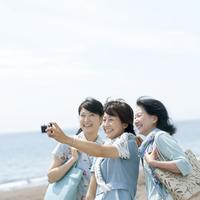 海辺で写真を撮る親子とシニア女性
