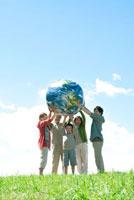 草原で地球のボールを持つ3世代家族