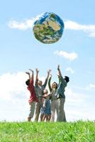 草原で地球のボールを投げる3世代家族