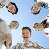 下を覗き込み微笑む3世代家族