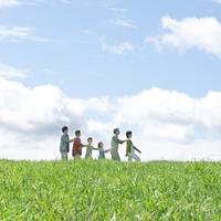 草原を一列に並んで歩く3世代家族