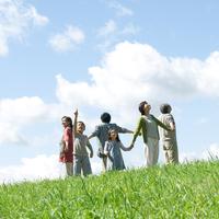 草原で手をつなぎ微笑む3世代家族