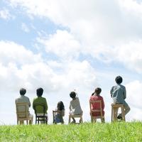 草原で椅子に座る3世代家族の後姿